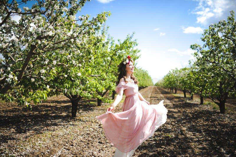 Ståenden av en härlig ung flicka i en rosa färg för flygbrudanbud klär på en bakgrund av det gröna fältet, skrattar poserar hon o royaltyfri bild