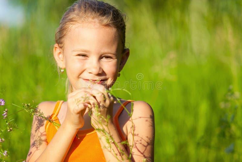 Ståenden av en härlig ung flicka med vildblommor parkerar in arkivbild