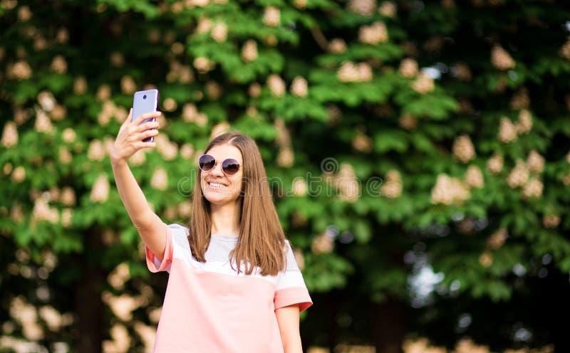 Ståenden av en härlig ung kvinna i solglasögon tar selfie med en smartphone arkivfoton
