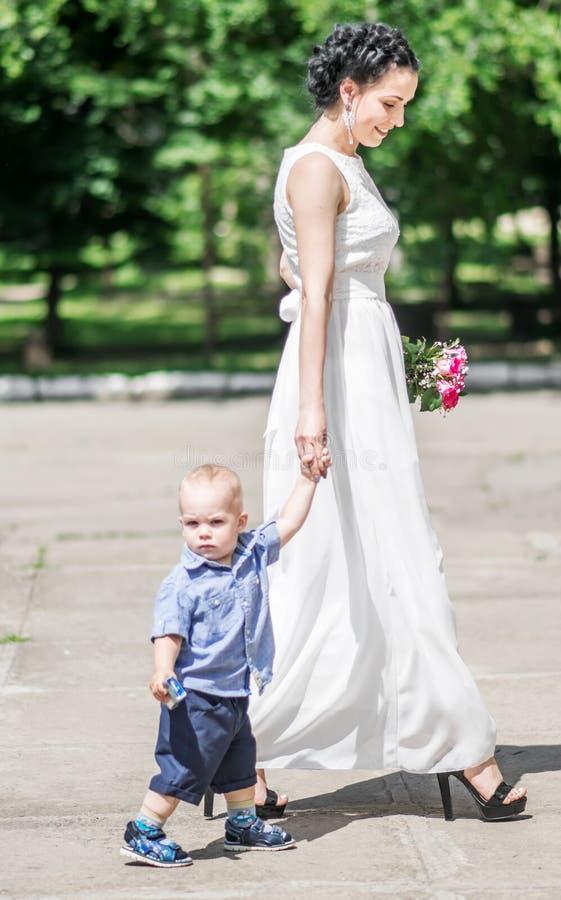 Ståenden av en härlig ung kvinnlig brud som går med litet, behandla som ett barn pojken till bröllopceremoni Fostra och hennes li arkivfoton