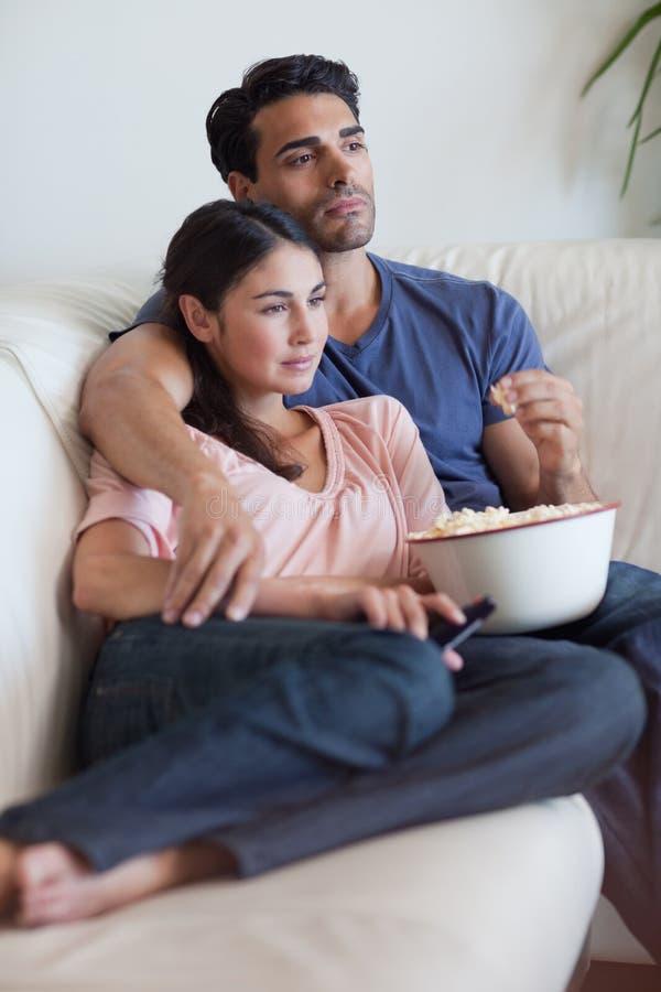 Ståenden av en hållande ögonen på television för koppla ihop fördriver äta popcorn fotografering för bildbyråer