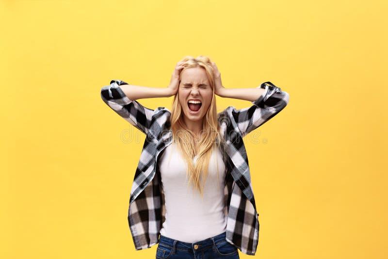 Ståenden av en ilsken irriterad kvinna med händer lyftte att ropa på kameran som isolerades på gul bakgrund fotografering för bildbyråer