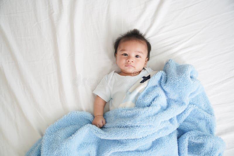 Ståenden av en krypning behandla som ett barn på sängen i hennes rum som är förtjusande behandla som ett barn pojken i det vita s fotografering för bildbyråer
