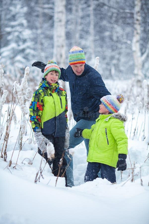 Ståenden av en lycklig familj i vinter parkerar Fader, son och litet skratta för dotter fotografering för bildbyråer