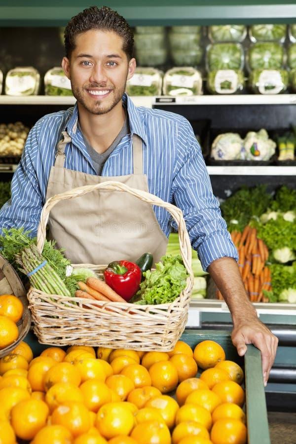 Ståenden av en lycklig man med grönsakkorgen som står near apelsiner, stannar i supermarket royaltyfri foto