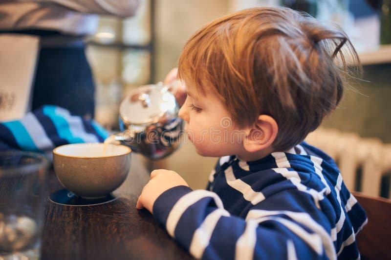 Ståenden av en lycklig pojke häller te in i en kopp hemma royaltyfri fotografi