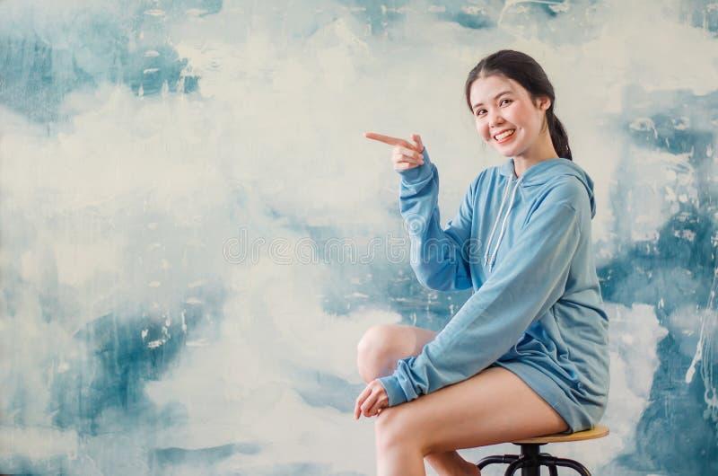 Ståenden av en lycklig ung sportflicka som bär modern sportkläder som pekar en, fingrar upp på kopieringsutrymme över färgrik bak royaltyfri fotografi