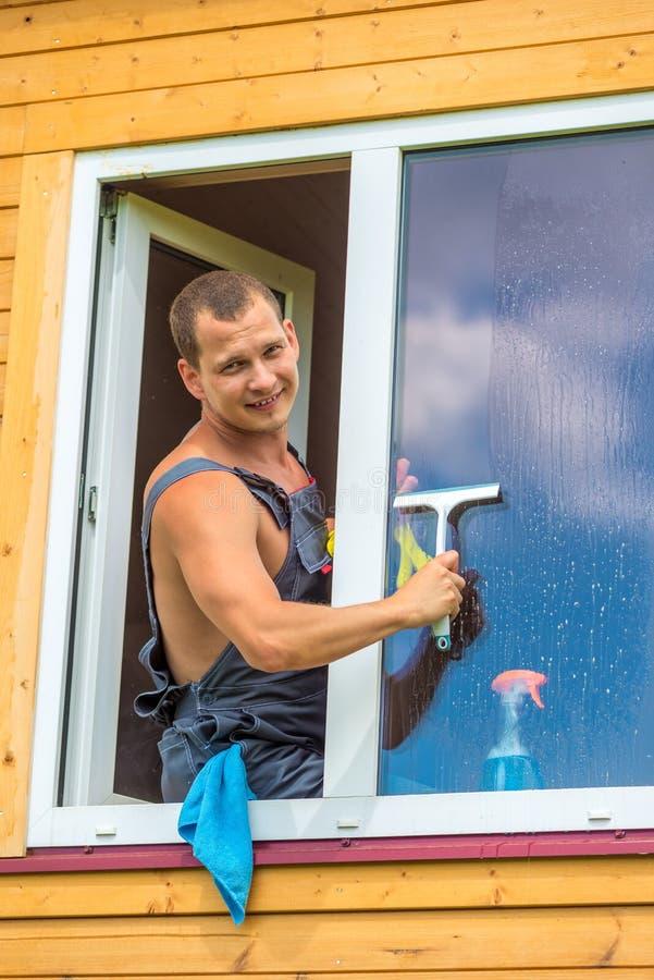 Ståenden av en man i overaller med hjälpmedel tvättar ett fönster royaltyfria bilder