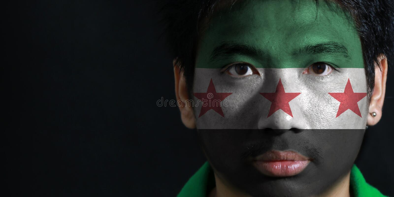 Ståenden av en man med flaggan av den syrianska provisoriska regeringen målade på hans framsida på svart bakgrund fotografering för bildbyråer