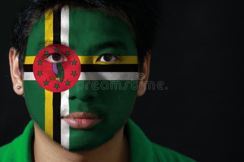 Ståenden av en man med flaggan av Dominica målade på hans framsida på svart bakgrund royaltyfri foto