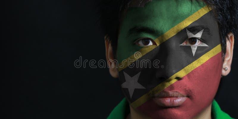 Ståenden av en man med flaggan av helgonet Kitts och Nevis målade på hans framsida på svart bakgrund arkivfoton
