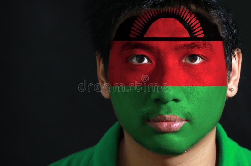 Ståenden av en man med flaggan av Malawi målade på hans framsida på svart bakgrund royaltyfri bild