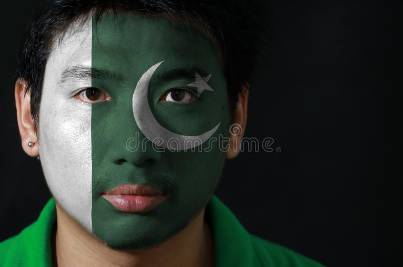 Ståenden av en man med flaggan av Pakistan målade på hans framsida på svart bakgrund arkivfoto