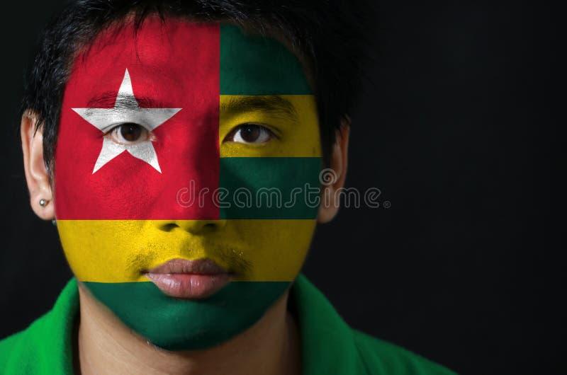 Ståenden av en man med flaggan av Togo målade på hans framsida på svart bakgrund royaltyfria bilder