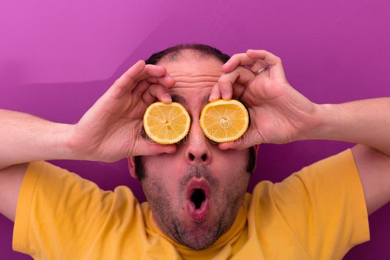 Ståenden av en man som rymmer två, skivade citroner i hans ögon royaltyfri fotografi