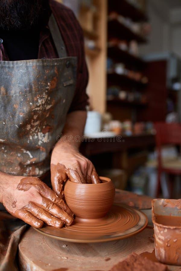 Ståenden av en manlig keramiker i förklädeformer bowlar från lera, den selektiva fokusen, närbild fotografering för bildbyråer