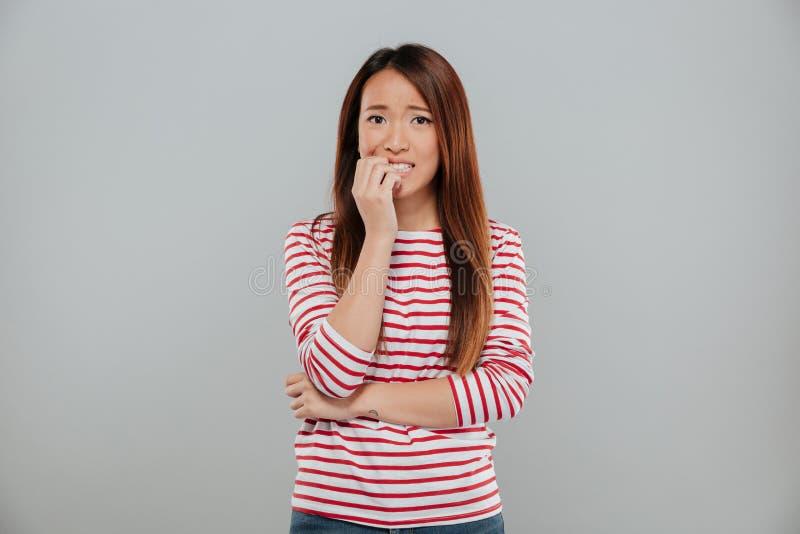 Ståenden av en nervös asiatisk flicka som biter henne, spikar arkivfoton