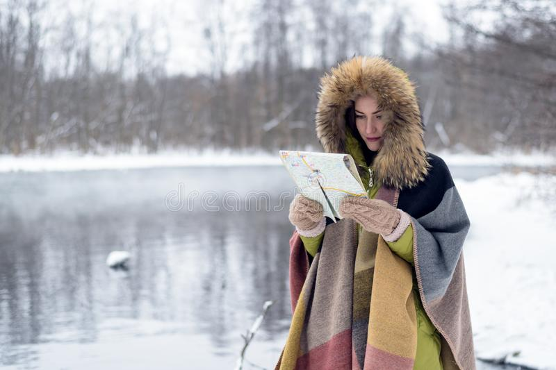 Ståenden av en resande kvinna i vinter beklär stående framme av sjön i vinterskogen med en översikt i den dimmiga morninen royaltyfri foto