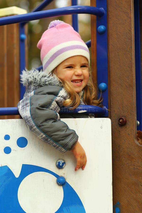 Ståenden av en rolig litet barnflicka på lekplats i hösten parkerar och att se i avståndet som gör framsidor royaltyfria bilder