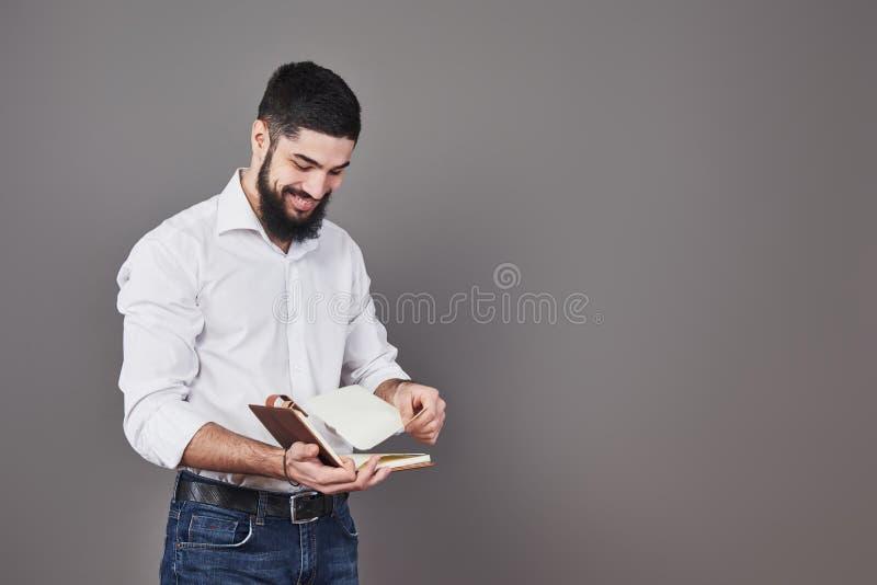 Ståenden av en skäggig ung man som bär en vitt skjorta och innehav en öppen stadsplanerare och, drar ut sidan En grå vägg arkivbild