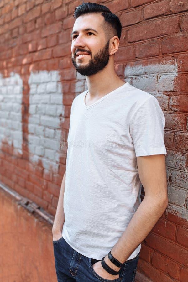 Ståenden av en stilfull och positiv grabb, i en vit tom t-skjorta, mot den orange tegelstenväggen, kan användas för annonsering,  fotografering för bildbyråer