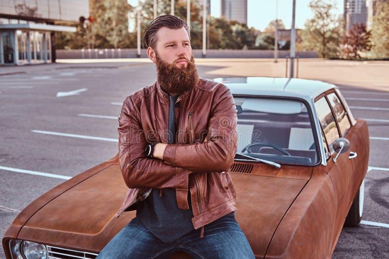 Ståenden av en stilfull skäggig man i gammalmodig kläder sitter på den retro bilen för huven i stadsparkeringen arkivfoto