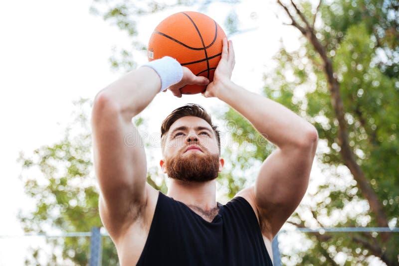 Ståenden av en stilig man i sportar bär att spela basket arkivbild
