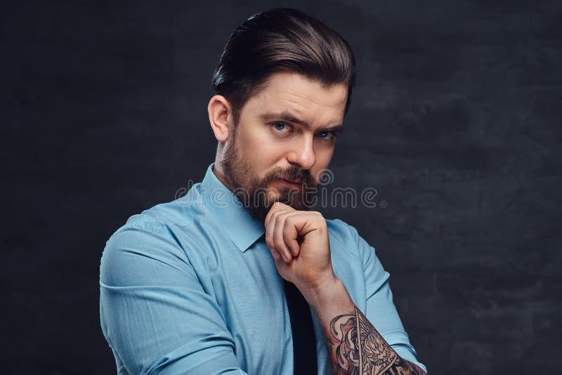 Ståenden av en tatuerad stilig medelålders man med skägget och den iklädda frisyren en blått skjorta och band, poserar i a royaltyfria foton