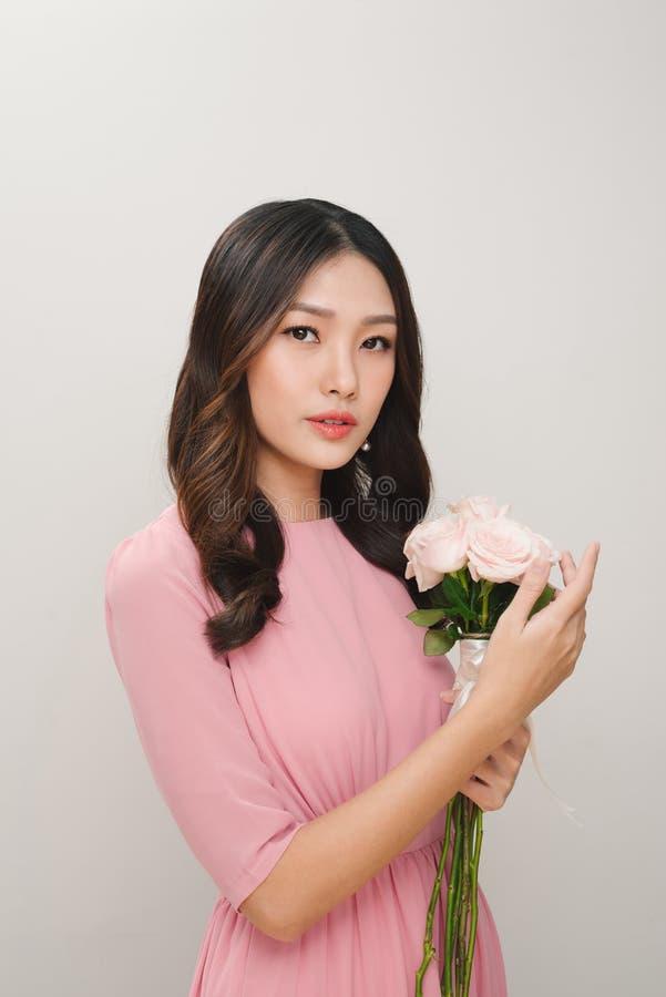 Ståenden av en tillfredsställd iklädd rosa färg för ung kvinna klär holdin royaltyfri foto
