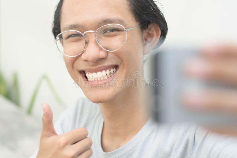 Ståenden av en ung attraktiv man som tar bilder av honom själv- eller selfiestund, ger upp tummen royaltyfri bild