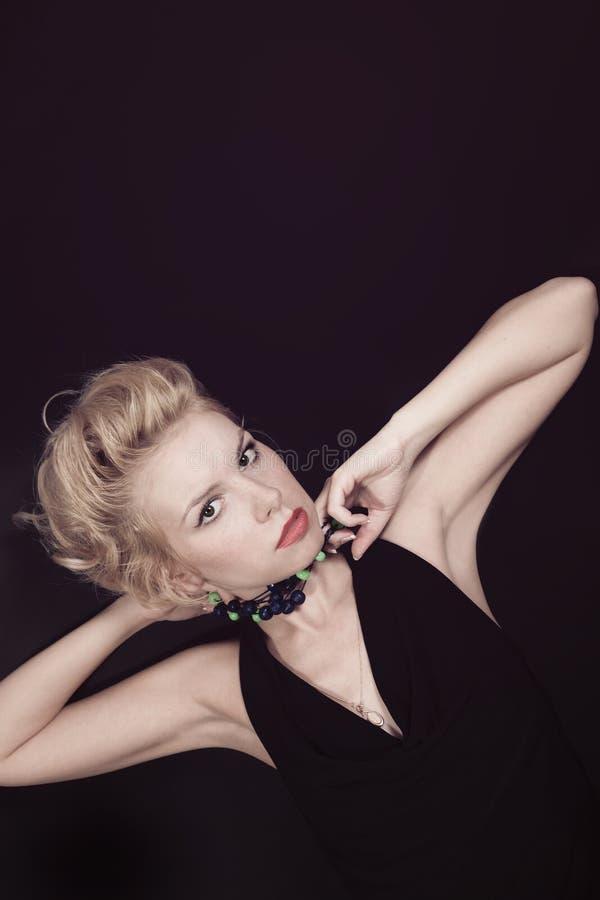 Ståenden av en ung blond kvinna med pryder med pärlor royaltyfri foto