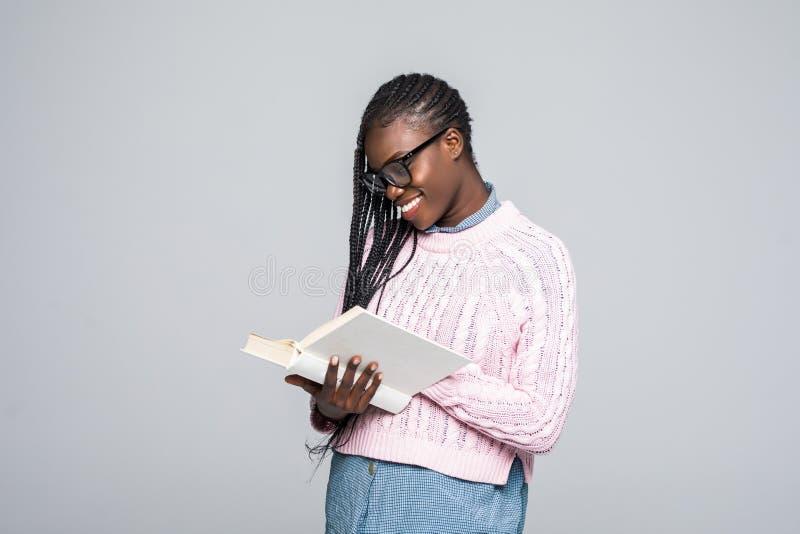 Ståenden av en ung härlig kvinna läser en bok med exponeringsglas som isoleras över grå bakgrund royaltyfria foton