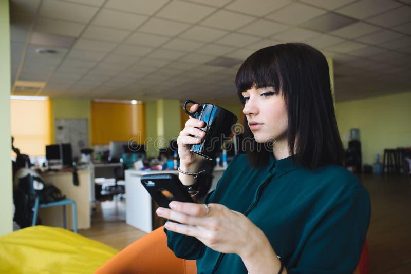 Ståenden av en ung härlig kvinnakontorsarbetare, som dricker kaffesvartkoppen, och använder en mobiltelefon bryt arbete royaltyfri foto