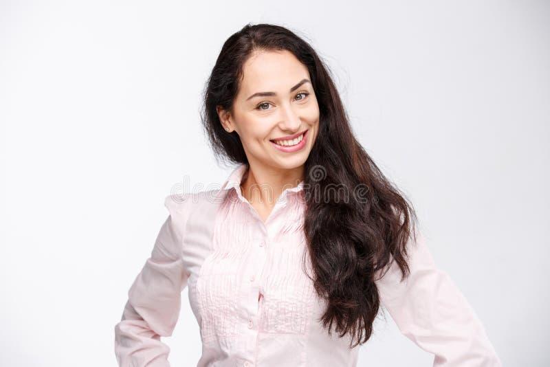 Ståenden av en ung kvinna med ett charmigt toothy leende, ett svart hår och en brunt synar på en vit bakgrund i en rosa skjorta p royaltyfria foton