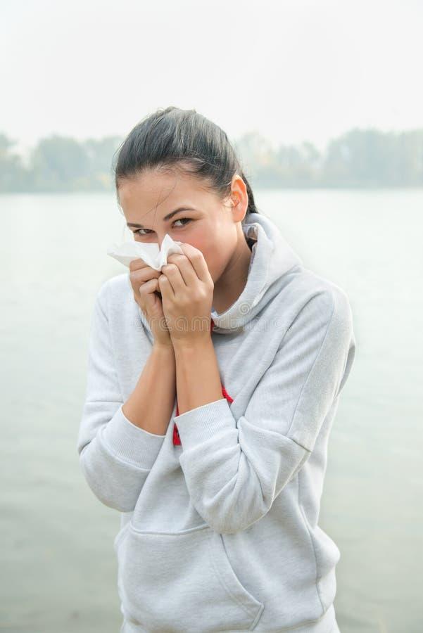 Ståenden av en ung kvinna med snörvlar eller allergireaktion arkivfoton
