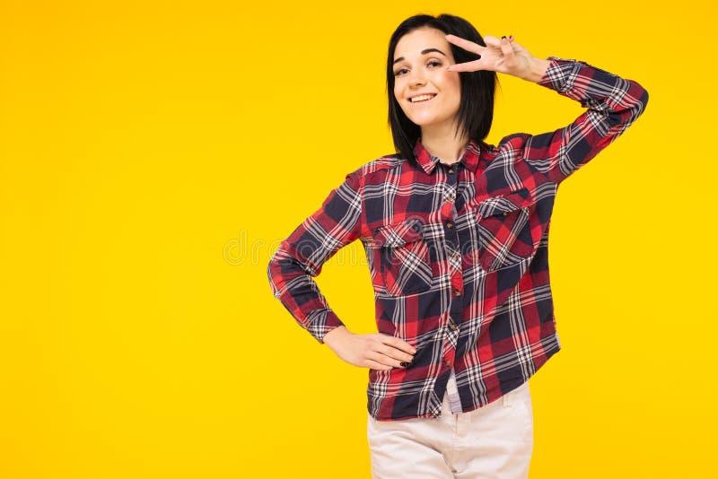 Ståenden av en ung kvinna som ser och visar fredhanden, sjunger på bakgrund royaltyfria bilder