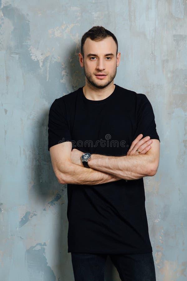 Ståenden av en ung man i en svart T-tröja lutade mot en tappninggrå färgvägg kopiera avstånd royaltyfria bilder
