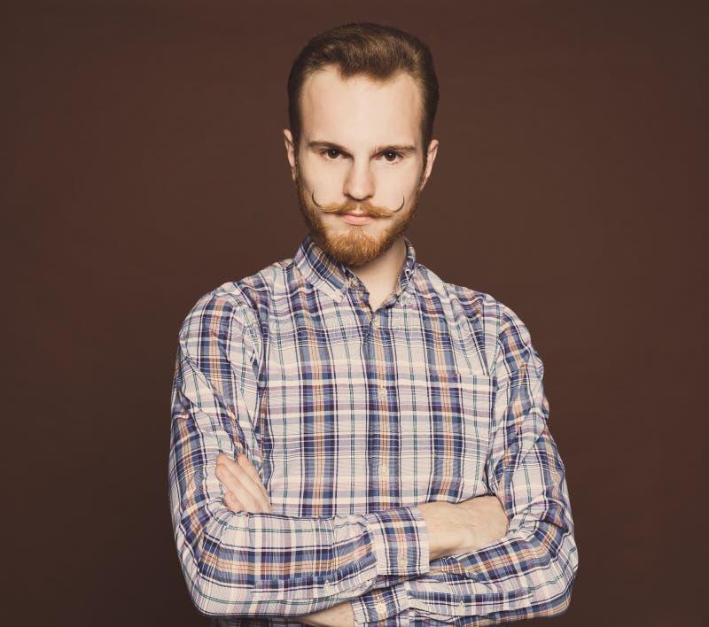 Ståenden av en ung man med den mustasch- och skäggjeans- och för en plädskjorta hipsteren utformar i studion Tonad färg inomhus royaltyfri fotografi
