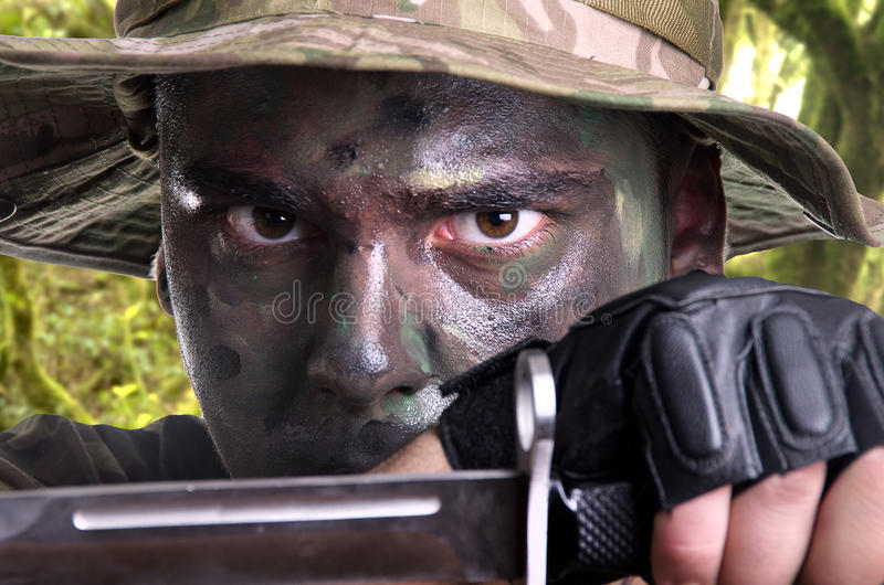 Ståenden av en ung soldat målade med djungelkamouflage royaltyfri foto