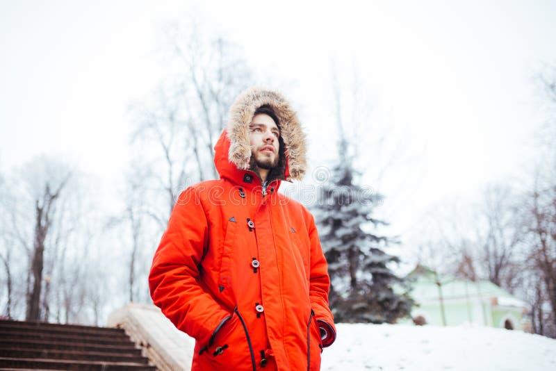 Ståenden av en ung stilfull man med det iklädda röda vinteromslaget för skägget med huven och päls på hans huvud står mot bakgrun arkivfoto