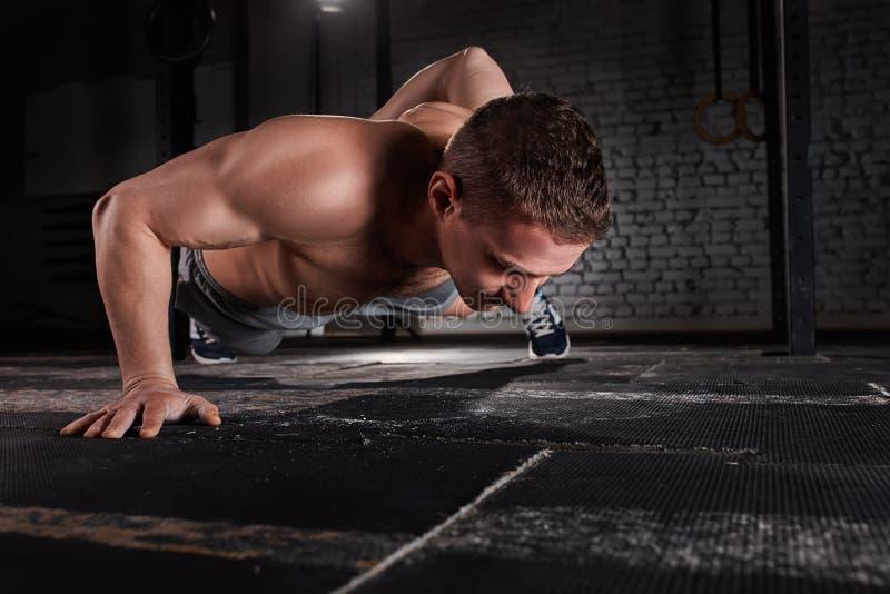 Ståenden av en ung stilig idrottsman som att göra skjuter, ups övning med en hand mot tegelstenväggen i konditionidrottshall royaltyfria bilder
