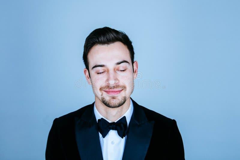 Ståenden av en ung stilig man i en dräkt och en fluga som ler, ögon stängde sig royaltyfria bilder