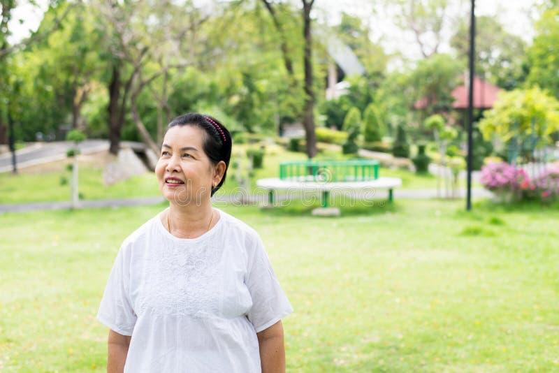 Ståenden av ett äldre asiatiskt kvinnaanseende och att se något på parkerar, lyckligt och att le arkivfoton