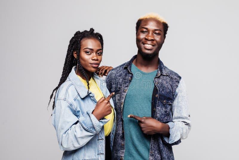 Ståenden av ett älskvärt ungt afro amerikanskt par som pekar fingrar på de, isolerade över vit bakgrund fotografering för bildbyråer