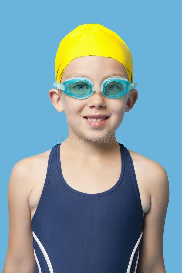ståenden av ett bärande bad för lycklig ung flicka rullar med ögonen över blå bakgrund royaltyfria bilder