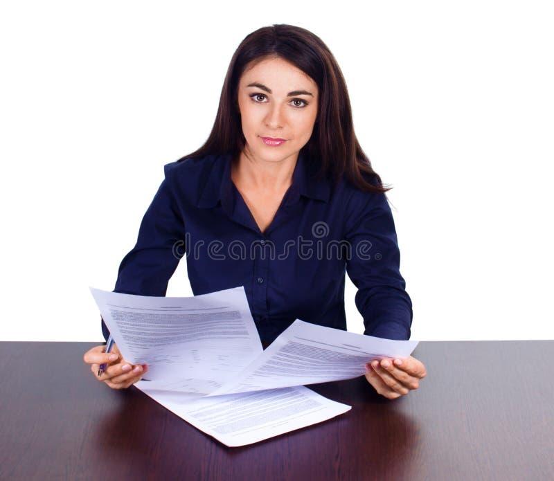 Ståenden av ett gladlynt sammanträde för affärskvinna på hennes skrivbord och undertecknar upp avtalet på vit bakgrund royaltyfri foto