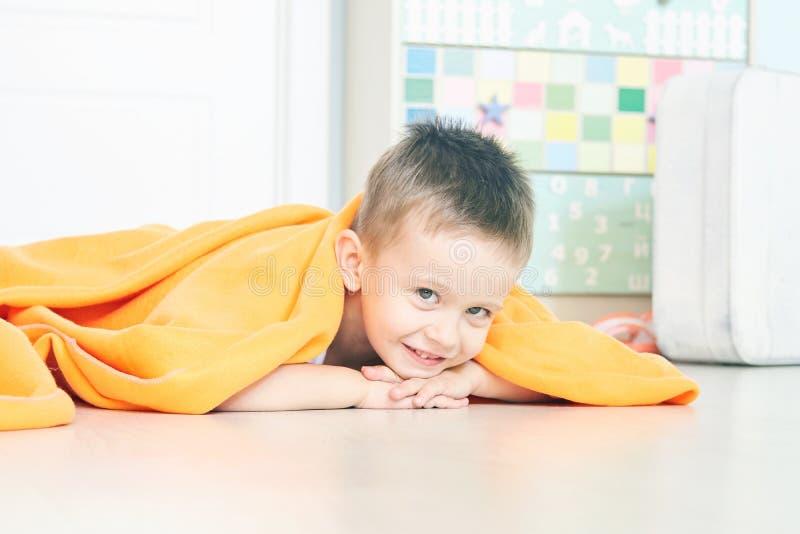 Ståenden av ett gulligt behandla som ett barn i orange pläd i hem arkivfoton