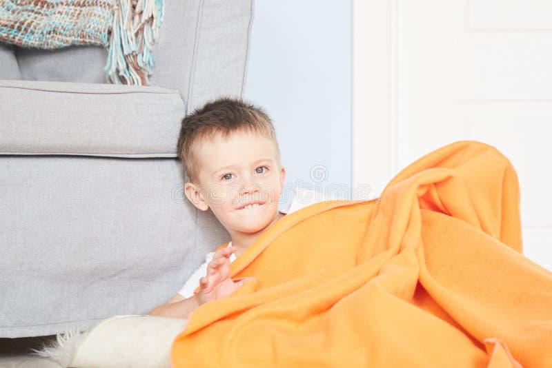 Ståenden av ett gulligt behandla som ett barn i orange pläd i hem royaltyfria foton