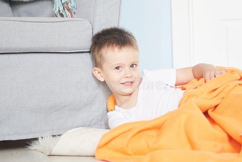 Ståenden av ett gulligt behandla som ett barn i orange pläd i hem royaltyfri foto