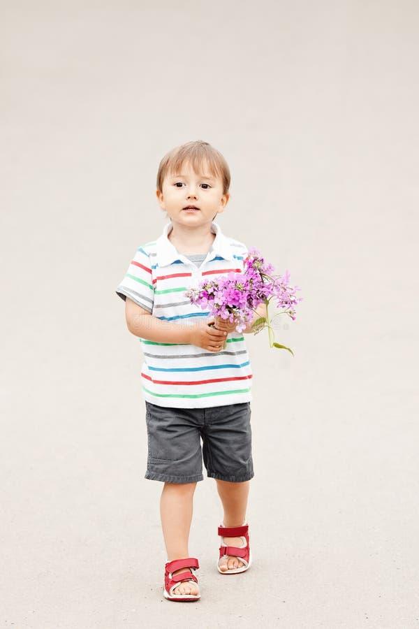 Ståenden av ett gulligt förtjusande roligt litet le pojkelitet barn som in går, parkerar med lila purpurfärgade rosa blommor i hä royaltyfria bilder